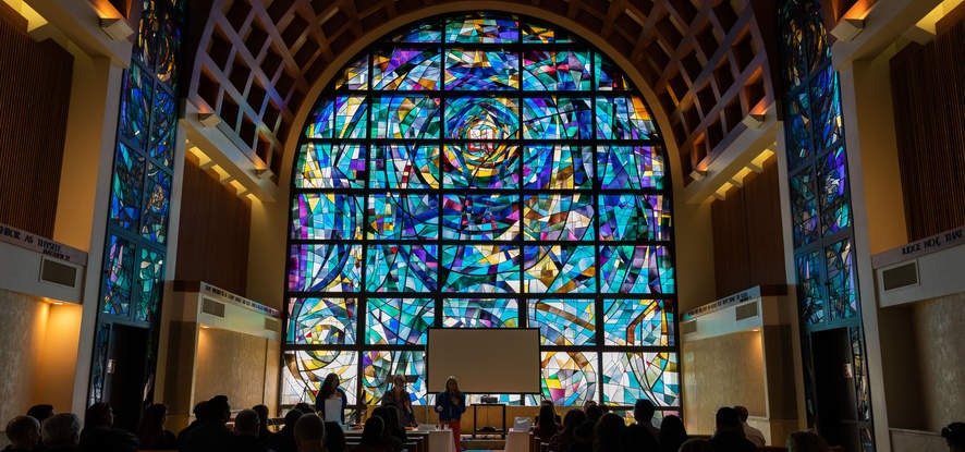 Students and parents are gathered in Stauffer chapel, looking at the front, of the reflection from the stained glass
