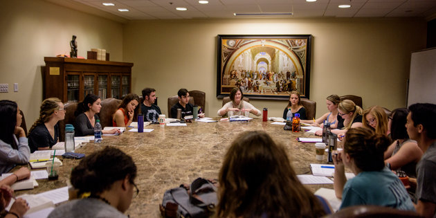 Students seated around a round table in the Great Books Room in Payson Library