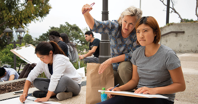 Professor teaching a student outside pointing to the distance