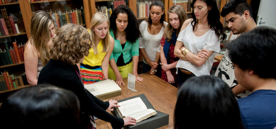 Academics, a group of students looking at an old manuscript from Pepperdine's special collections
