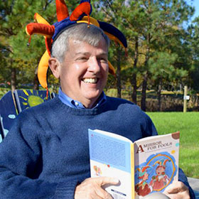 Terry Lindval sits in a chair with a huge grin and a children's book