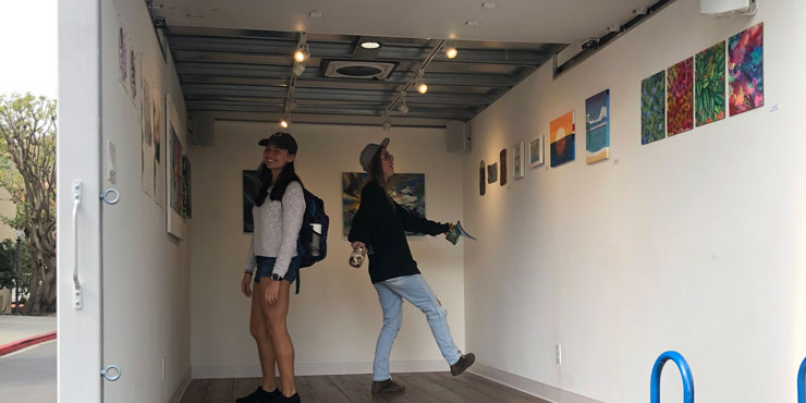 Two female students admiring artwork on the walls inside Pepperdine's mobile art gallery