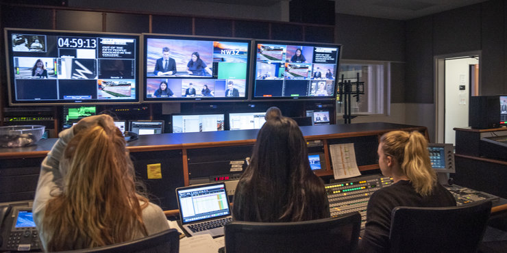 Back of Seaver students pictured in the NewsWaves control room, looking at multiple screens
