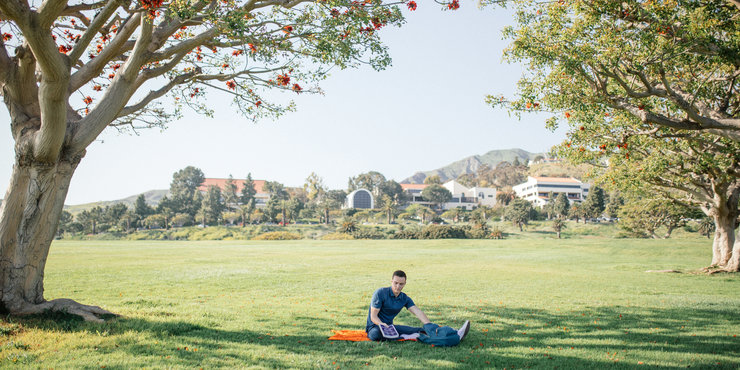 Male student sitting on an orange blanket on alumni park, unpacking books to study