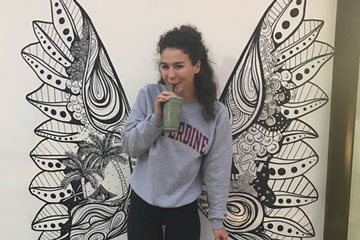 Seaver student Grace Cummins pictured in front of a wall with wings