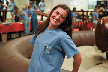 Lanie Jones photographed in her blue sorority shirt, pictured smiling in front of a mechanical bull