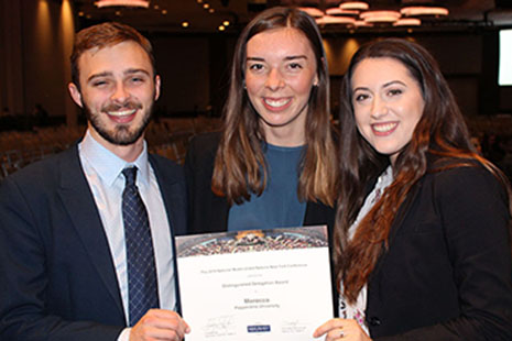 Three students holding Distinguished Delegation award.