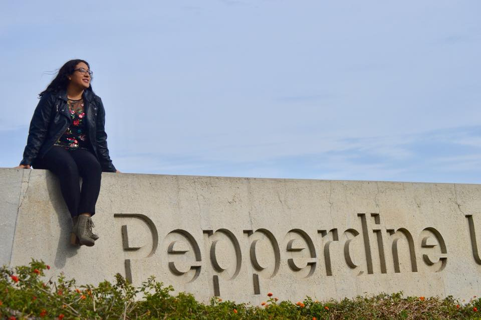 Seaver student sitting atop the Pepperdine University sign in Malibu