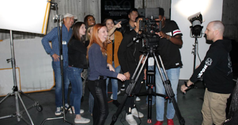 Seaver students gathered around a film camera at RED Studios
