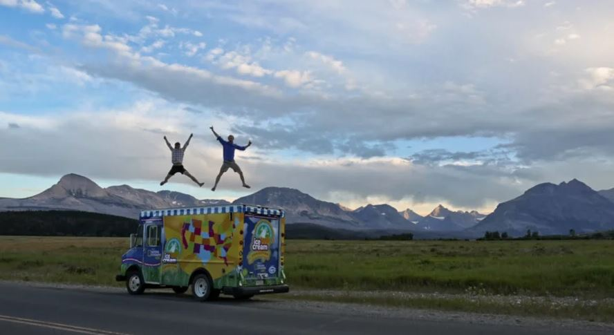 Two men jumping on top of a ice cream truck