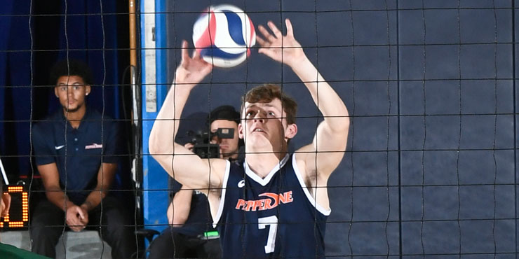 Spencer Wickens on the volleyball court, palms open, about to serve a volleyball over the net