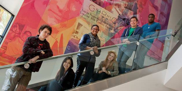 Advertising majors line up on a staircase inside a building - Advertising Degree