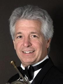 Joseph Meyer smiles brightly in a classic head shot holding a brass instrument.
