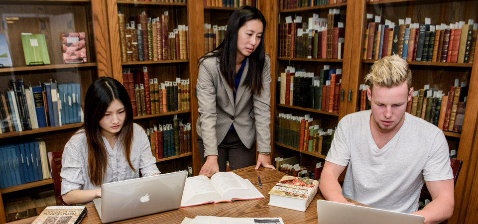 Two students sit around a round table while a smiling faculty member stands beside them in a large library.