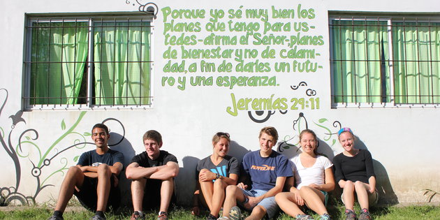 Spanish majors sit against a wall mural with a Spanish biblical phrase - Spanish Degree
