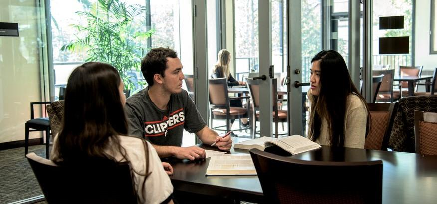 Three students gathered at a table inside the Student Success Center