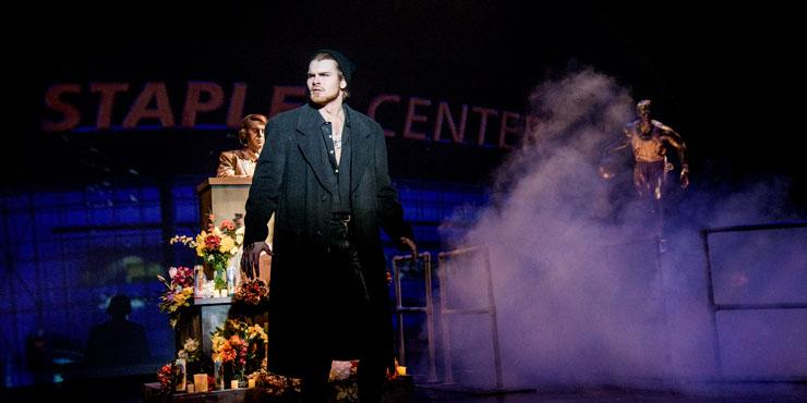 Male opera student, center stage, dressed in a black coat