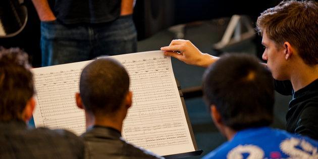 Music majors read sheet music during a concert rehearsal - Music Degree