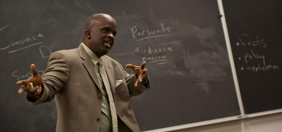Pepperdine professor photographed in the classroom, in front of a blackboard