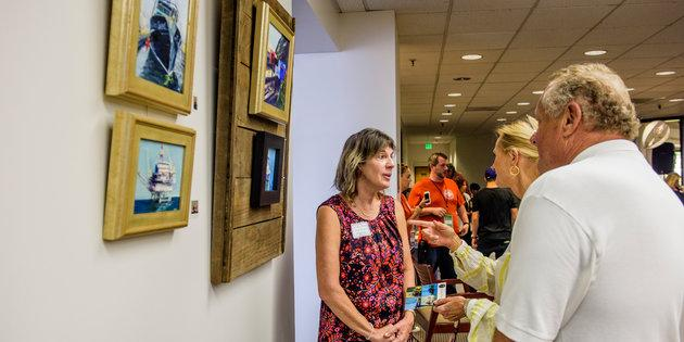Seaver alumni discussing their artwork besides framed paintings