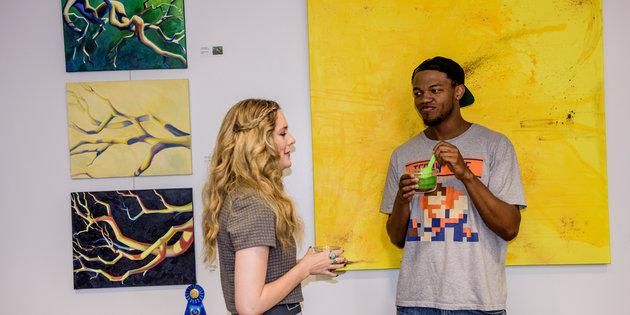 Seaver alums discussing their art in front of a yellow painting