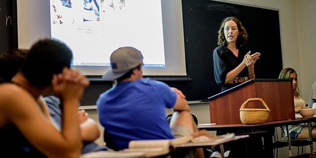 Two male students are listening intently to a female professor at the front of the class