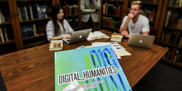 Two students sitting around a table with a close-up of a Digital Humanities textbook