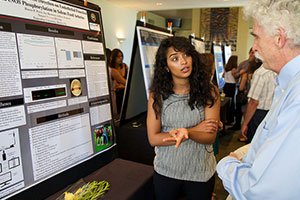 Pepperdine student sharing research and poster