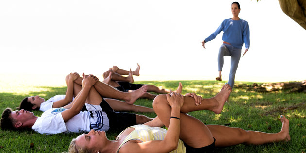 Sports medicine majors perform exercise routines on the grass - Sports Medicine Degree