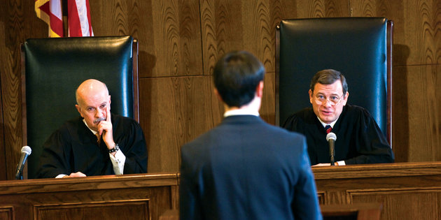 An attorney addresses two judges in a courtroom