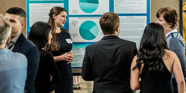Students presenting their research via a poster session on campus