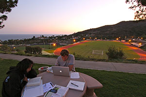 two students studying on campus at dusk